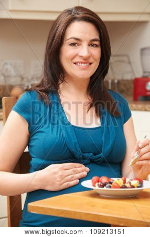 Pregnant Woman Eating Bowl Of Fresh Fruit In Kitchen