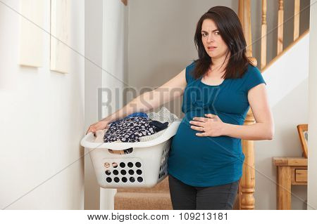 Stressed Pregnant Woman Doing Chores At Home