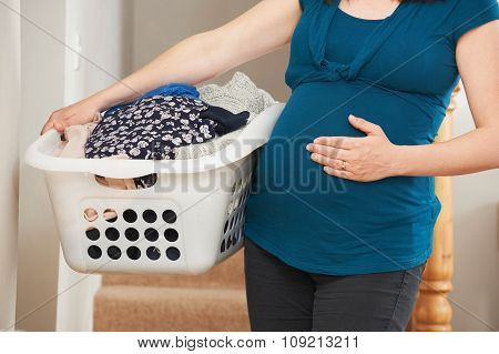 Close Up Of Pregnant Woman Doing Laundry At Home