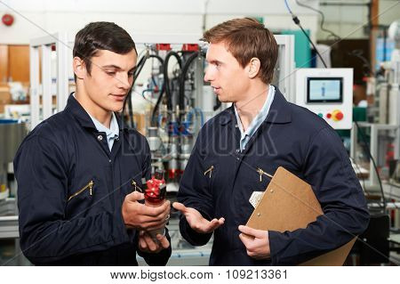 Engineer And Apprentice Discussing Component In Factory