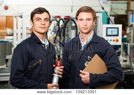 Portrait Of Engineer And Apprentice In Factory