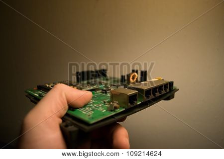 Hand holding an switch motherboard