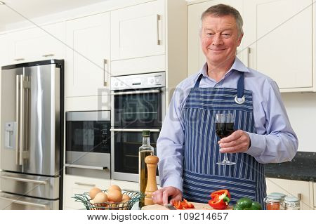 Senior Man Enjoying Cooking In Kitchen With Glass Of Wine