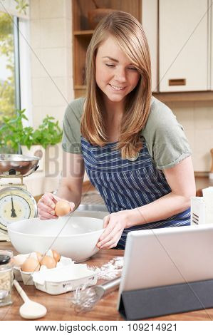 Woman Cooking And Following Recipe On Digital Tablet