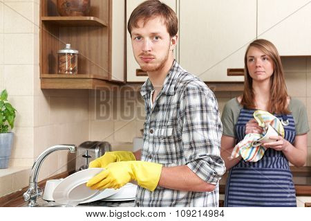 Man Reluctantly Washing Up In Kitchen With Partner
