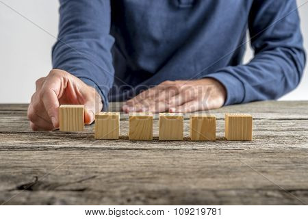 Man Placing Six Blank Wooden Cubes In A Row