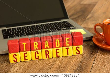 Trade Secrets written on a wooden cube in a office desk