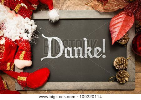 Blackboard with the text: Thank You (in German) in a christmas conceptual image