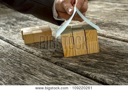 Male Hand Placing A Paper Roof On Top Of Miniature House