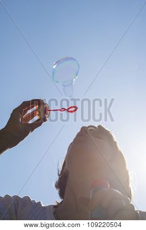 Closeup Of Young Woman Blowing Soap Bubbles