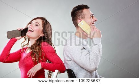Young Happy Couple Talking On Mobile Phones.