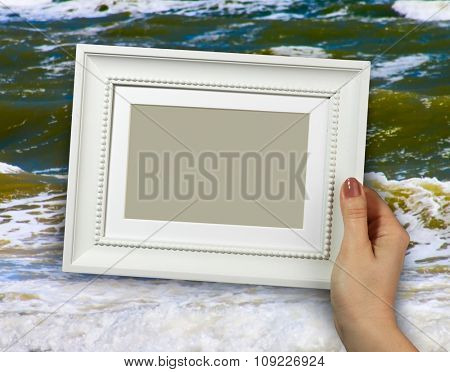 Wooden frame in beautiful woman hands on the background sea waves on beaches, sands, foam