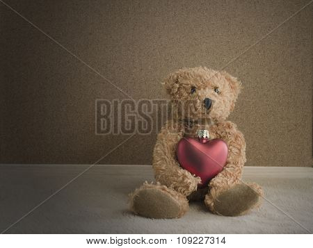 Teddy Bear Sitting With Red Heart Background