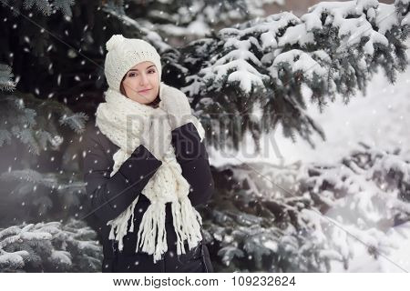 Portrait of a young pretty woman outdoors under snowfall.