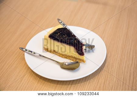 Blueberry Cheesecake With Little Spoon In A Plate On Wood Table