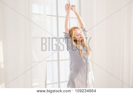 Smiling pleased sleepy blonde woman in striped pajamas waking up and stretching near big window