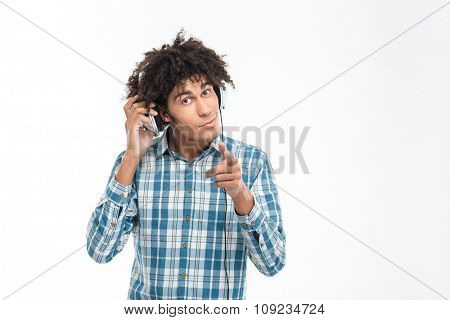 Portrait of a afro american man listening music in headphones and pointingfinger at camera isolated on a white background