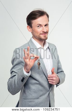 Portrait of a happy businessman showing ok sign and thumb up isolated on a white background