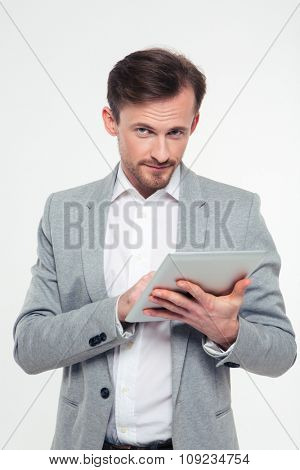 Portrait of a serious businessman using tablet computer and looking at camera isolated on a white background