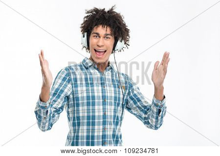 Portrait of a cheerful man in headphones looking at camera isolated on a white background