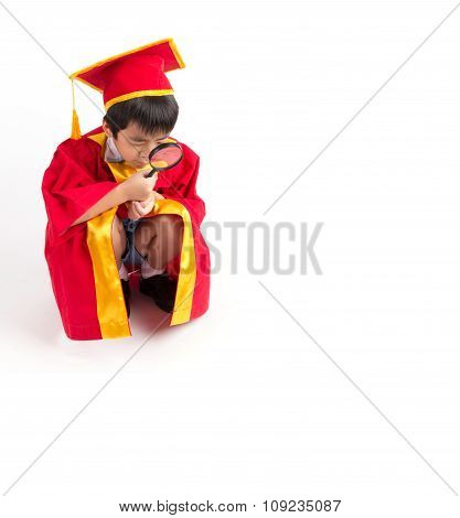Portrait Of Curious Boy In Red Gown Kid Graduation With Mortarboard Looking Something Through Magnif