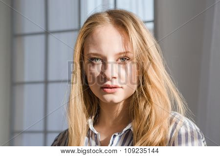 Portrait of attractive sensual young female with blonde hair in striped pajamas