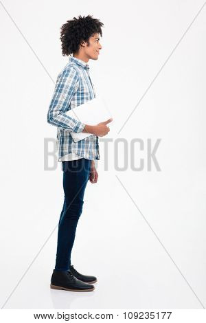 Side view portrait of a happy afro american man standing with laptop computer isolated on a white background