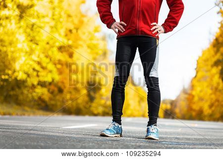 Legs of the athlete standing on the autumn road