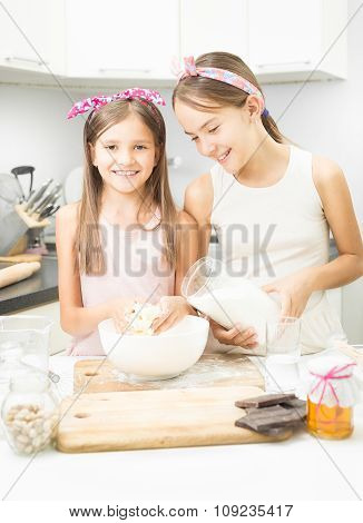 Elder And Young Sister Making Dough On Kitchen In White Bowl