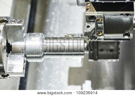 metalworking  industry. cutting steel metal shaft processing on lathe machine in workshop. Selective focus on tool