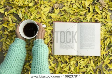 Woman Hands Holding Cup Of Coffee Over Leaves Background.
