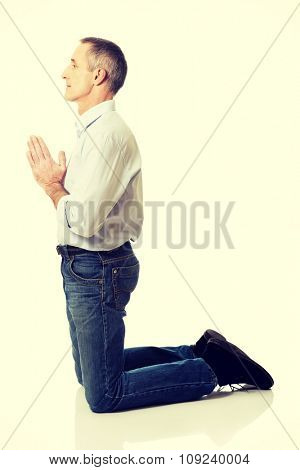 Handsome mature man praying to God on knees.