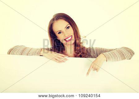 Beautiful happy woman pointing on blank board.
