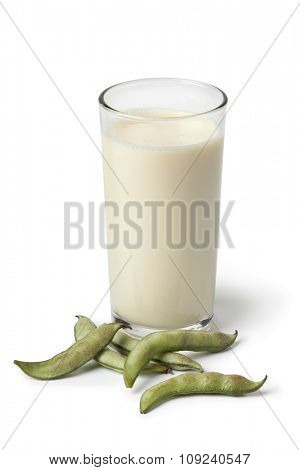 Glass of soy milk and fresh soybeans in the pod on white background