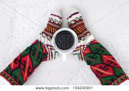 Cup Of Coffee And Female Feet With Socks On A White Carpet,