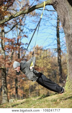 outdoor suspension training in forest - caucasian  man at tree