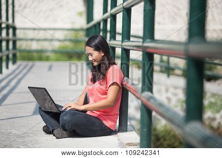Young Asian Student Sitting Outdoor, Using A Laptop