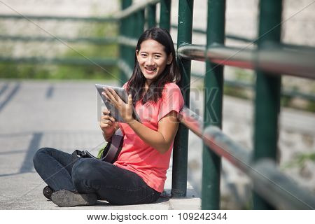 Young Asian Student In Her Outdoor Activity, Holding A Tablet Pc While Sitting.