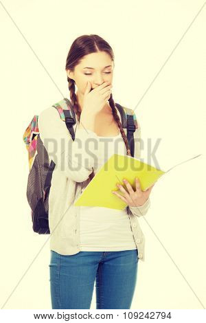 Yawning teenager girl with school backpack holding folder.