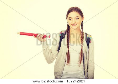 Happy schoolgirl pointing aside with pencil.