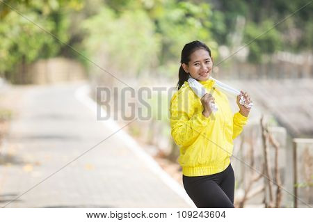 Young Asian Woman After Exercising Outdoor In Yellow Neon Jacket