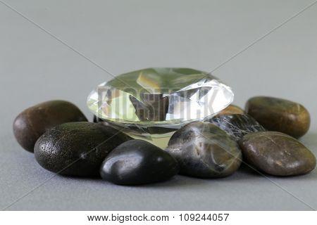 large glass diamond among ordinary gray stones
