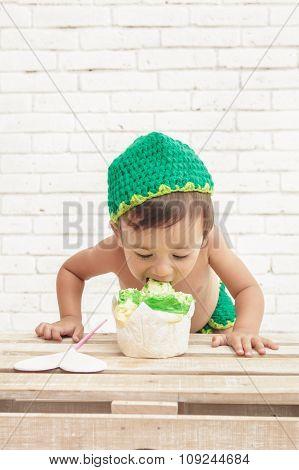 Toddler Wearing Green Hat Eating A Sponge Cake
