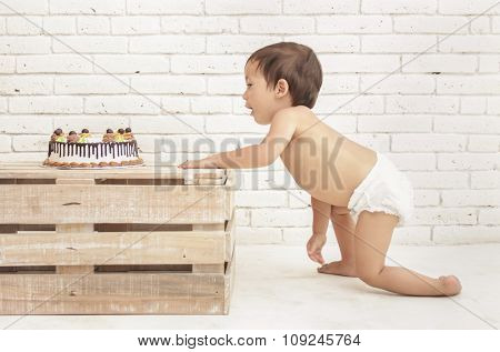 Toddler Wearing Diapers Crawling Into His Cake