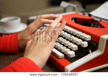 human hands writing on old red typewriter