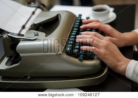 closeup of woman typing with old typewriter side view
