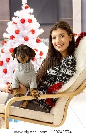Attractive woman smiling happy holding dog on lap, sitting front of christmas tree.