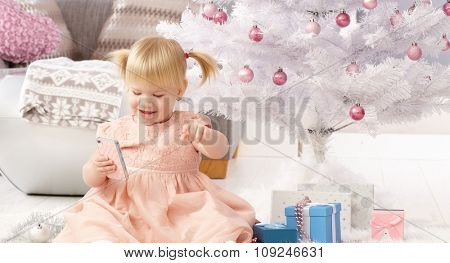 Cute little girl sitting by christmas tree with mobilephone, smiling.
