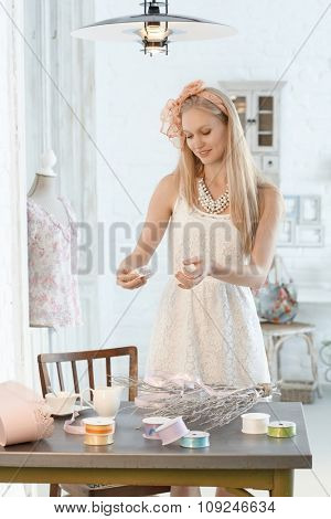 Young woman making decoration in romantic retro style.