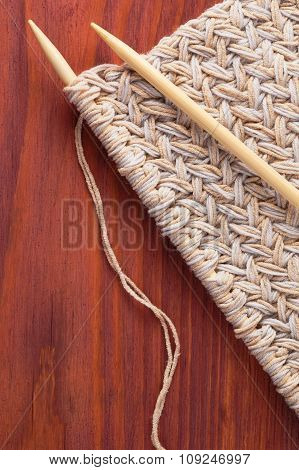 Piece Of Knitted Cloth With Wooden Needles On Wooden Table